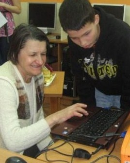 Young volunteers teach seniors to use computers in the library, helping to break down barriers between the generations.