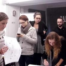 Students reading documents at a workshop in Poland.