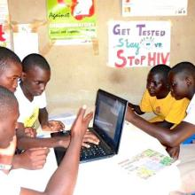 Teenagers using laptops to research the internet for health information in their library.