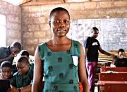 Young girl in school uniform in school classroom.