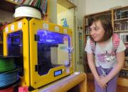 in photo litttle girl looking at 3D printer