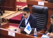 MP Dastan Bekeshev at a desk, addressing the meeting, through a microphone