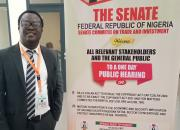 Desmond Oriakhogba next to a poster advertising the Senate hearing.