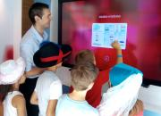 Children in the bank using a touch screen to learn about bank services