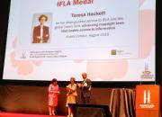 Teresa Hacket receives the award at the IFLA congress. Backdrop is of a banner of Teresa.