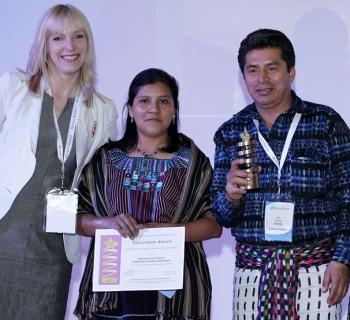 Ugne Lipeikaite of EIFL presents an Innovation Award for Using ICT to empower women to Rija'tzuul Na'ooj Library (Guatemala), represented by Petrona Garcia Hernandez and Rodolfo Antonio Perez Yperez, mayor of San Juan la Laguna.
