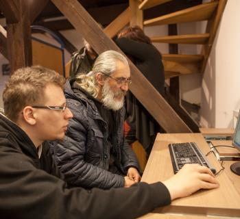 a young volunteer teaches an older, homeless man to use a computer in the library