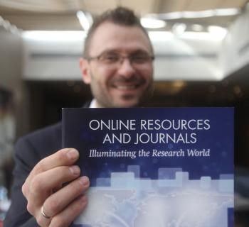 An EIFL publisher partner holds up a pamphlet about e-resources at the EIFL General Assembly
