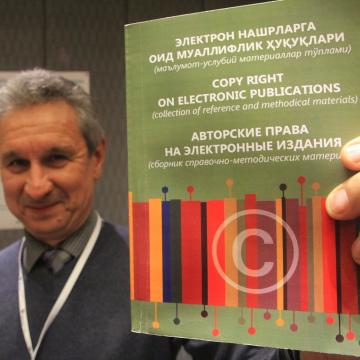 Photo of EIFL's country coordinator in Uzbekistan proudly holds up a new booklet 'Copyright on Electronic Publications' translated from EIFL resources. The booklet is available in Russian and Uzbek.