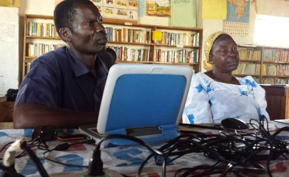 Two farmers learning computer skills in Caezaria Public Library in Uganda.