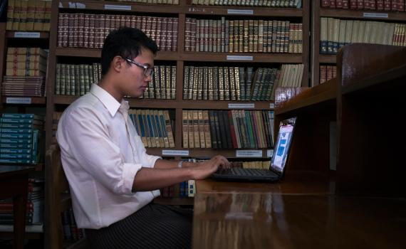Young man studying at the computer in Myanmar library.