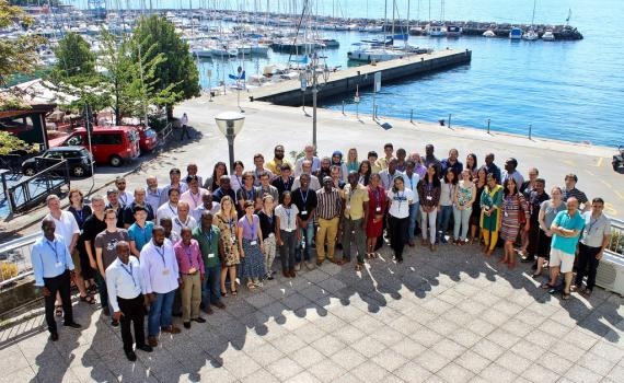 A large group of people, smiling, near the sea in Trieste.