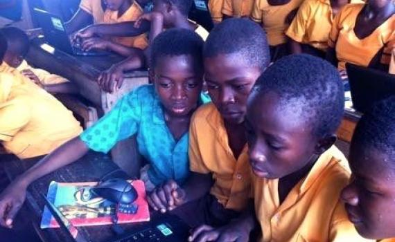 Ghanaian children in a classroom crowding around a computer.