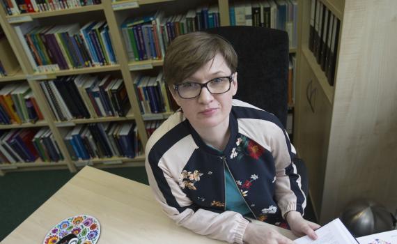 EIFL Copyright Coordinator in Poland, Barbara Szczepańska, sitting at her desk, with bookshelves in the background.
