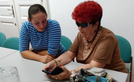 Senior using smart phone, with their trainer, in the library.
