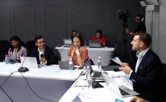 people addressing a panel discussion, at a table