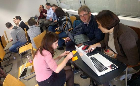 People sitting and working in groups open science trainer bootcamp in Debrecen, Hungary.