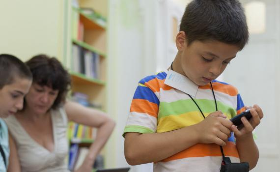 Child in the library using a mobile phone
