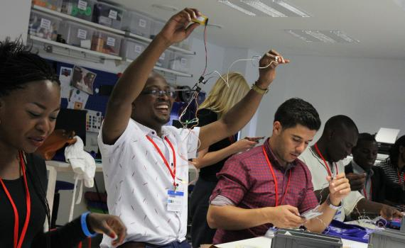 Young African public library innovators using tools during a hands-on experience in the National Library of Lithuania makerspace.