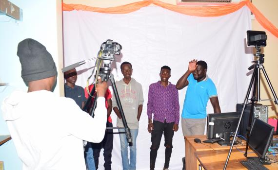 A group of young photographers try out the cameras and other equipment in the library.