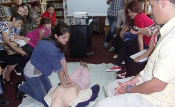 Library trainees practise using the First Aid dummy.
