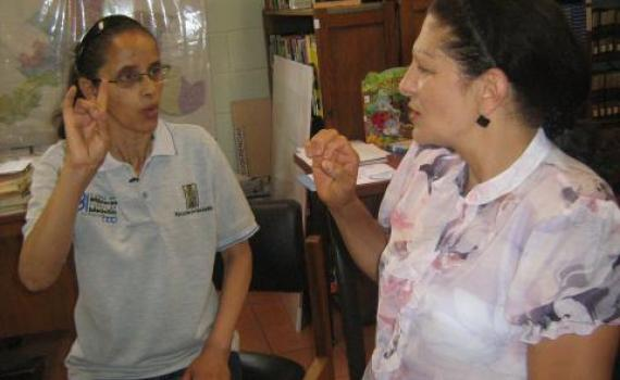 A  library trainee practises sign language with a librarian.