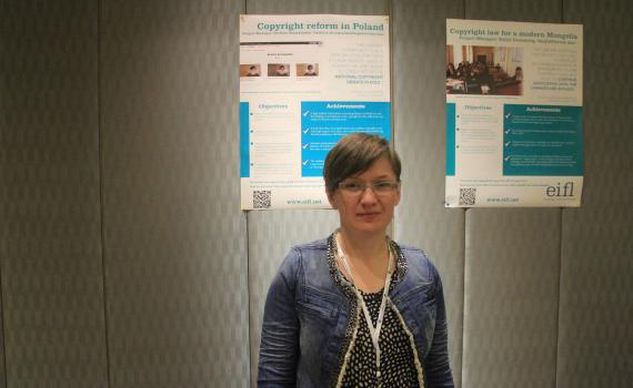 Project Manager, Barbara Szczepanska in front of poster of case study