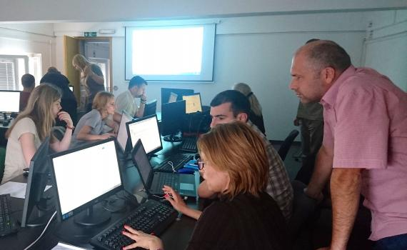 Editors and librarians entering information onto computers.