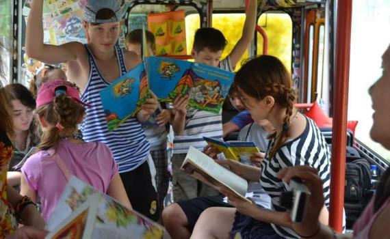 Children reading books inside the trolleybus.